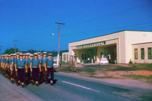 UNTD Cadets beginning route march or perhaps going to or from the rifle range (John MacFarlane) from front gates of HMCS Cornwallis, May/June, 1962. Photo by William Thomas, U-794.